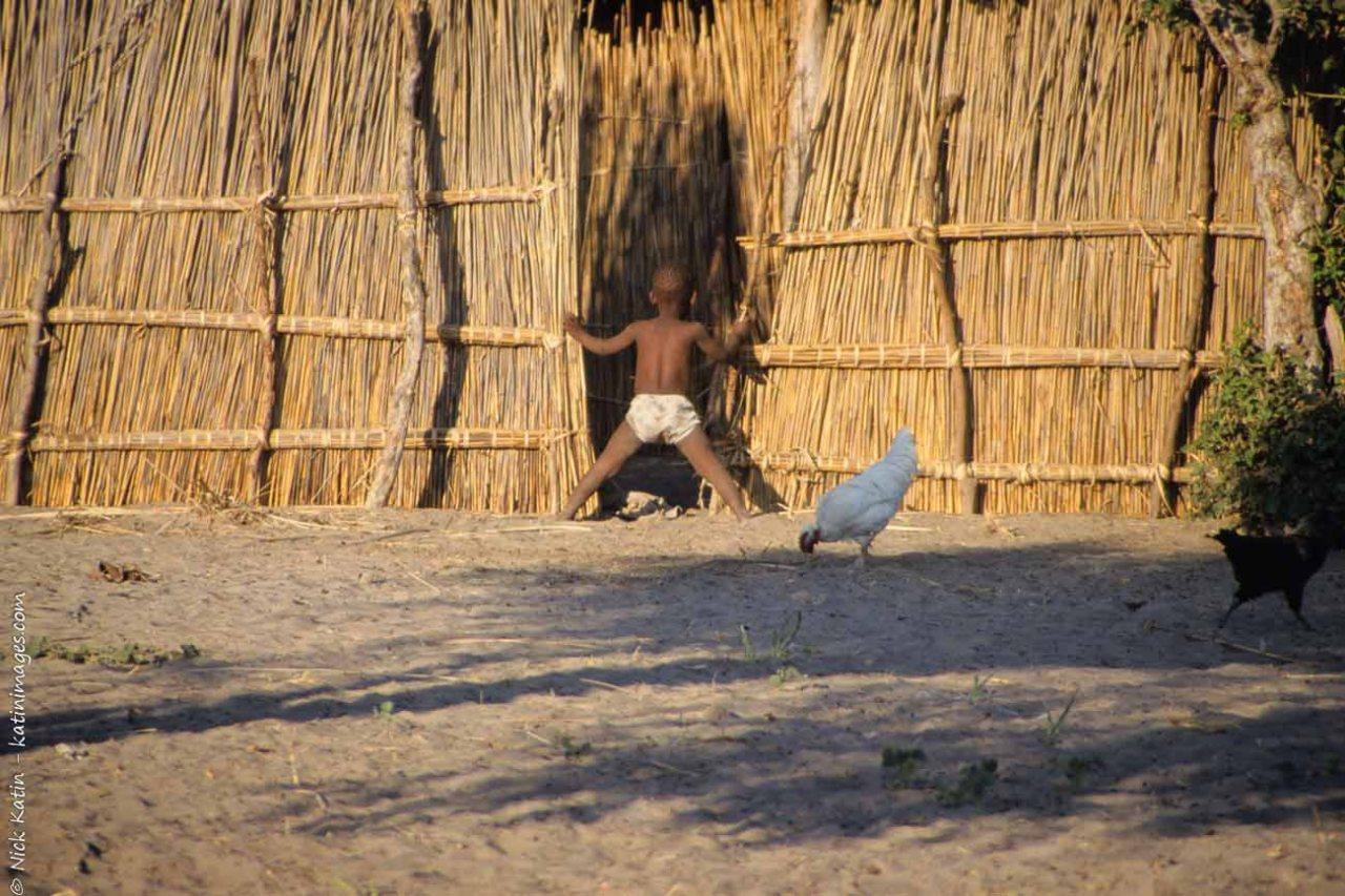 Young boy peeking in a hut in a small village in Botswana