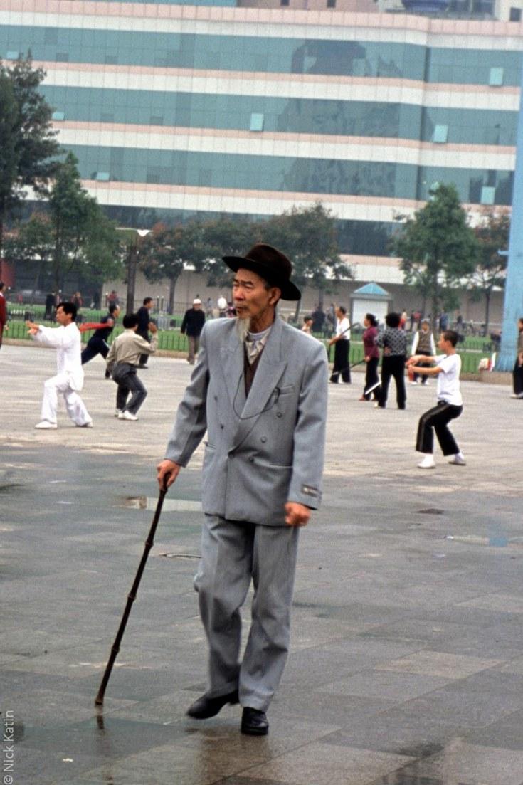 Well dressed man watching Tai Chi in Kunming's main square.