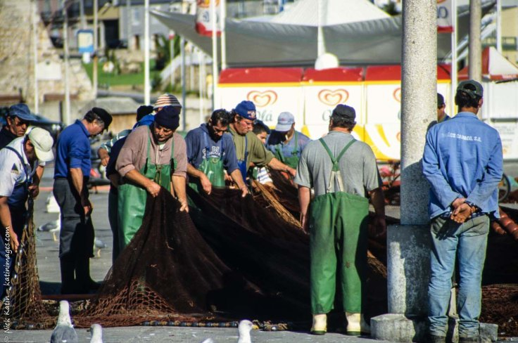 Fishereman organising their nets on the jetty in Peniche, Portugal