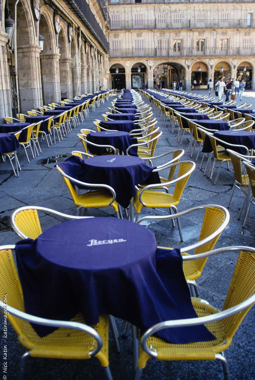 Empty tables waiting for customers at a alfresco restaurant, in Salamanca's Plaza Mayor in Spain