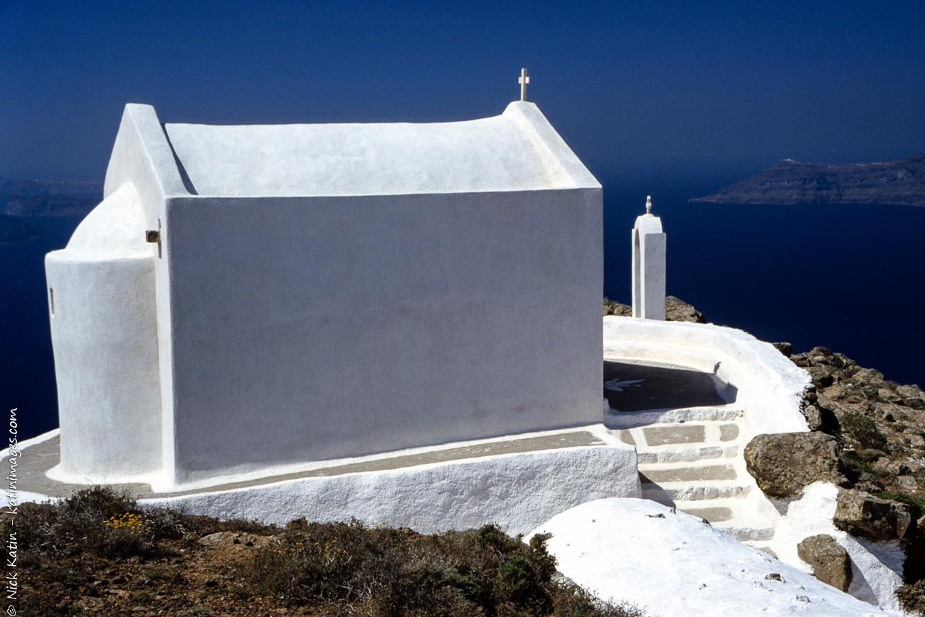 A small church sitting on the cliffside in Santorini, Greece