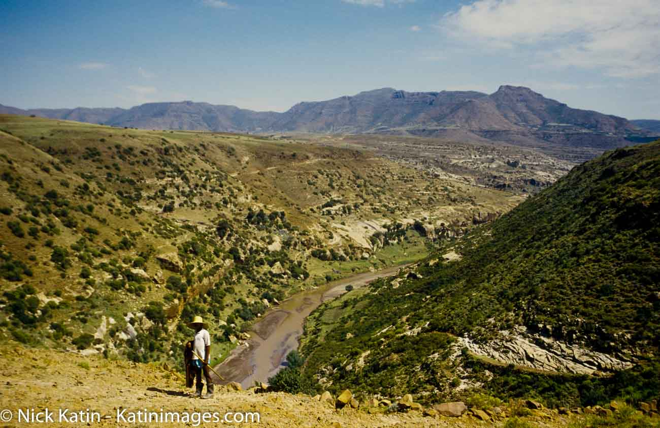 A sheep herder stands overlooking a gorge in the Maloti Mountains of Lesotho.