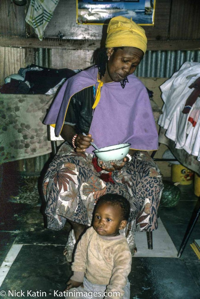 Mother and child in Soweto in the shadows of Soweto's upmarket and large homes are residential tin shacks. Soweto, South Africa.