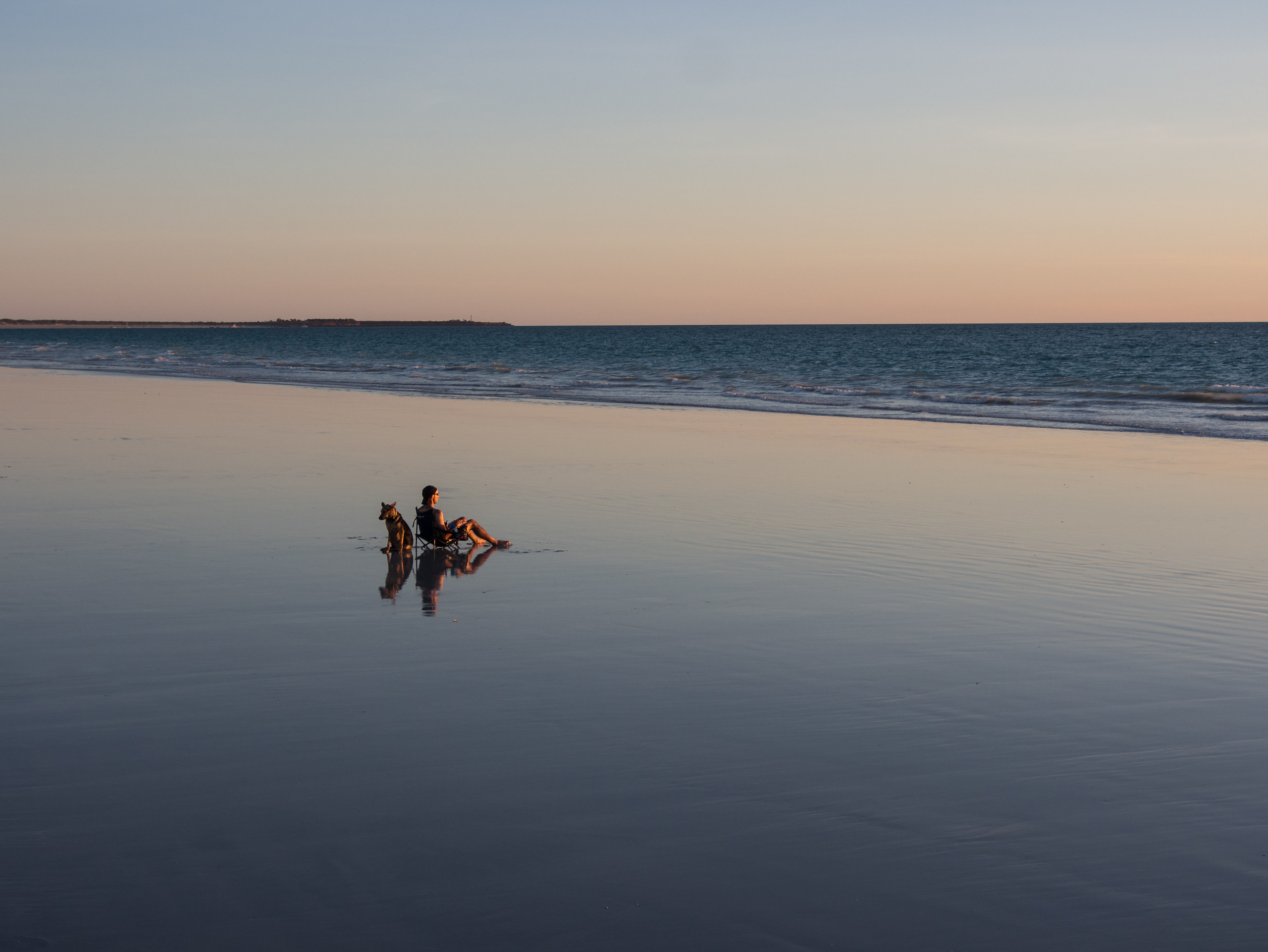 Man and his dog relaxing at Cable Beach, Broome, Western Australia
