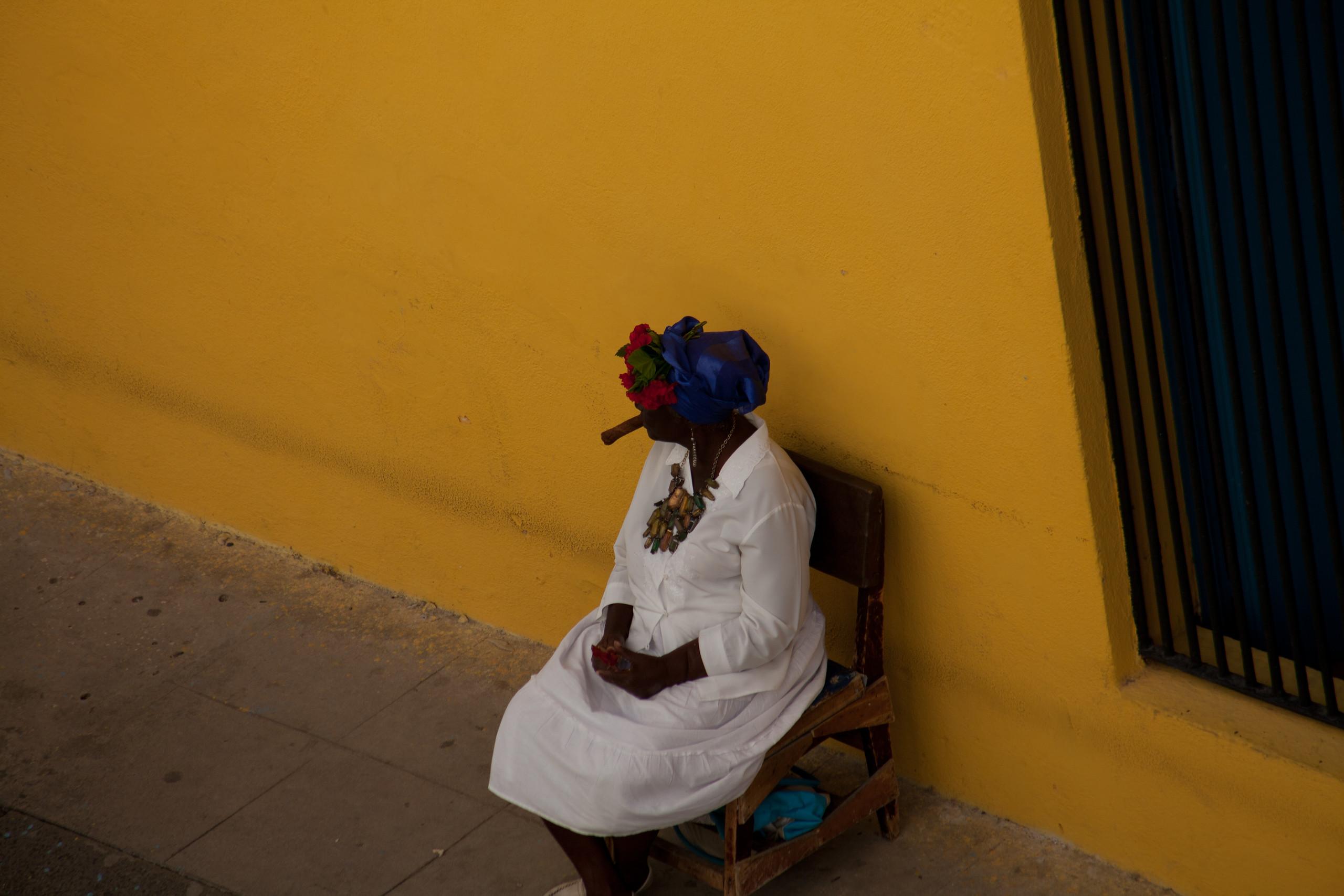 Cigar smoking fortune teller near Catedral Plaza, Havana